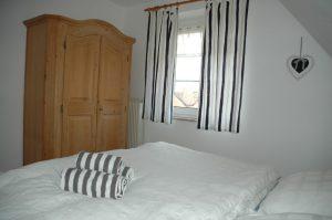 Schlafzimmer mit Doppelbett und Bauernschrank