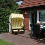 Terrasse mit Standkorb, Gartentisch und Stühlen