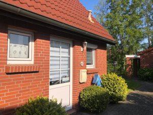 Rotes Backsteinhaus mit weißer Tür und weißen Fenstern