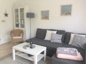 Graue Couch mit weißem Couchtisch